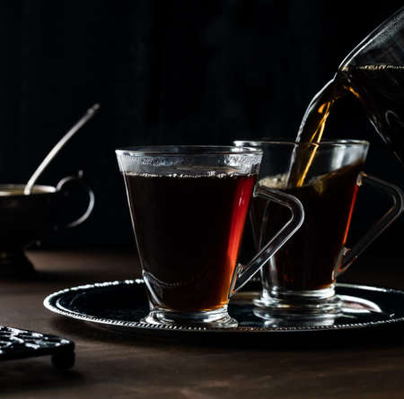 A close up of two cups of tea on a metal tray with tea being poured into one, against a black background.