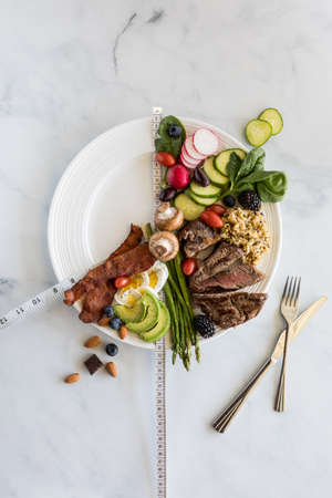 Intermittent fasting weight loss concept. Various low carb foods on a white plate against a white marble background.