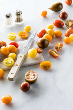 Colourful cherry tomatoes on a marble cutting board against a white background.
