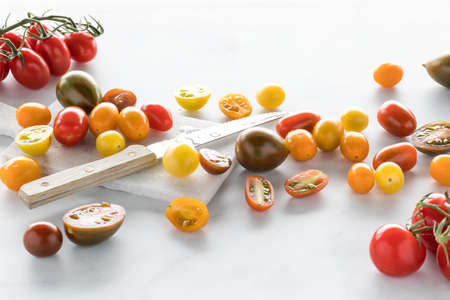 Assorted cherry tomatoes with a knife and cutting board against a white background. 版權商用圖片