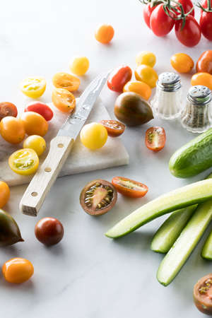 Assortment of cherry tomatoes and cucumbers cut up on a marble cutting board against a white background.