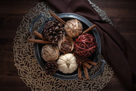 Top down view of a vintage dish filled with autumn ornaments, on a dark wooden table.