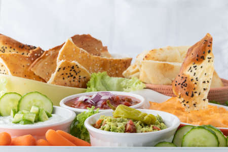 Various dips including buffalo chicken, guacamole and salsa with crisp breads and vegetables for dipping