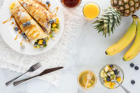 Top down view of tropical fruit crepes on a white plate surrounded by various breakfast foods.