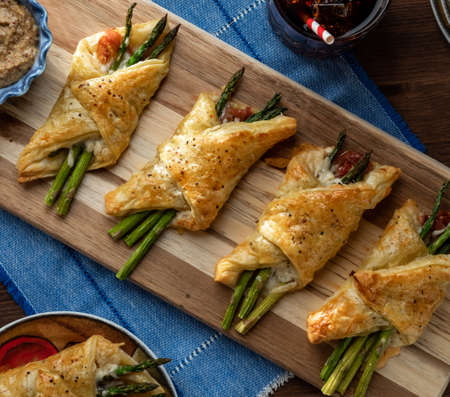 Close up of asparagus and prosciutto pastry bundles against a dark background with sunlight streaming in.