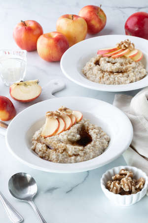 Two bowls of steel cut oats and brown sugar, garnished with apples