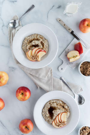 Top down view of bowls of steel cut oats and brown sugar garnished with apples and walnuts.