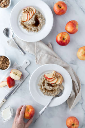Two bowls of steel cut oats with brown sugar and garnished with apple slices and walnuts.