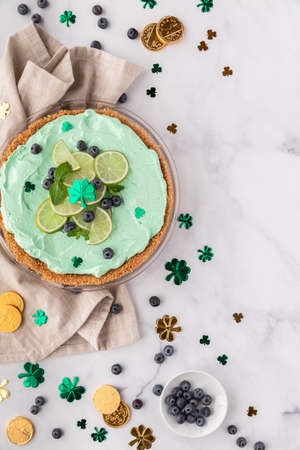 Top down view of a Key Lime Pie with St. Patricks Day decorations all around.