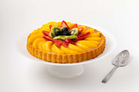Close up of a German fruit flan on a cake pedestal against a white background.