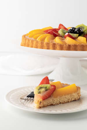 German fruit flan with one slice on a plate in front ready for eating.