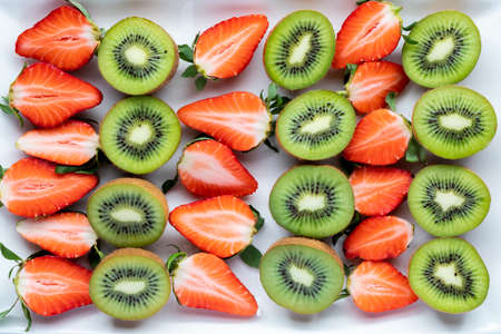 Rows of cut kiwis and strawberries. Complimentary fruit flavours