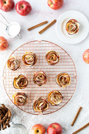 Top down view of pastry apple roses on a rose gold coloured cooling rack surrounded by apples and cinnamon sticks.