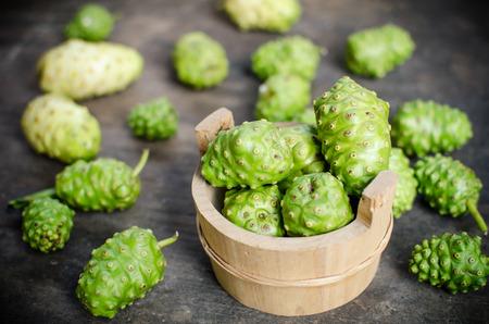 morinda: green Noni, Morinda citrifolia fruit in wood bowl on old desk Stock Photo