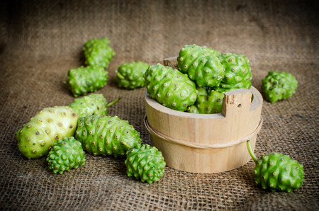 noni: green Noni, Morinda citrifolia fruit in wood bowl on brown sack