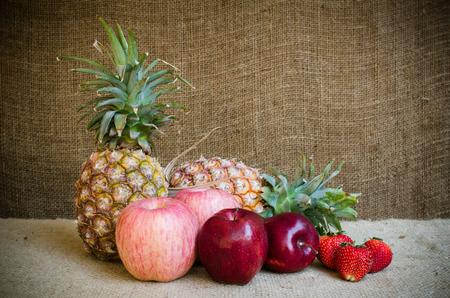 apple sack: Two pine apple strawberries and apple on brownish sack Stock Photo