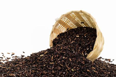black rice: Organic black rice in bamboo bowl on white background Stock Photo