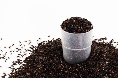 black rice: Organic black rice in plastic cup on white background