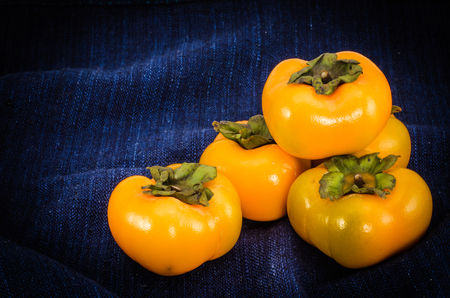 persimmons: Yellow persimmons on deep blue fabric