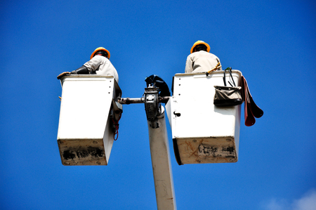 Electrical utility worker in a bucket on blue sky background photo