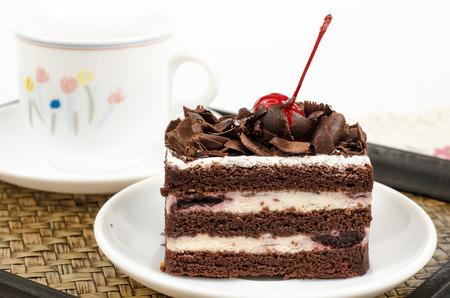 rebanada de pastel: Imagen de pastel de chocolate en un plato blanco con una taza de té en la bandeja de bambú tejido Foto de archivo