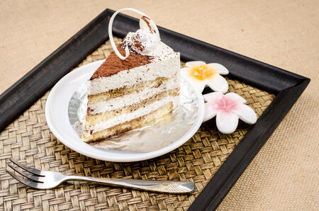cake in white dish on bamboo woven tray photo
