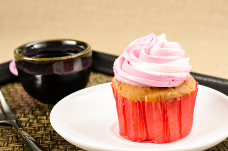 birthday cupcakes: Image of cup cake in white dish on bamboo woven tray Stock Photo