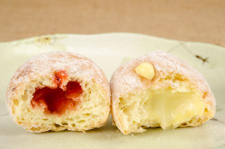 Afbeelding van donut bal met hap uit genomen in keramische schotel op bruine zak achtergrond Stockfoto