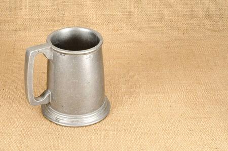 pewter mug: Image of old aluminium beer mug on white background brown sack background Stock Photo