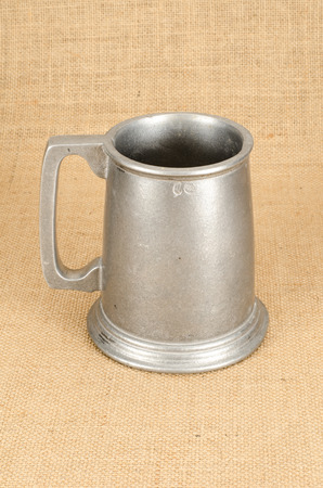 Image of old aluminium beer mug on white background brown sack background Stock Photo