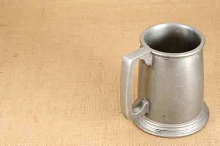pewter mug: Image of old aluminum beer mug on white background brown sack background