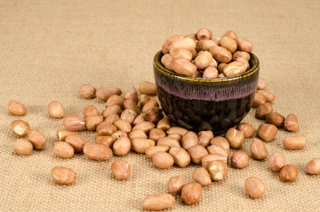 ground nuts: Image of raw peanuts in ceramic bowl  on brown sack background