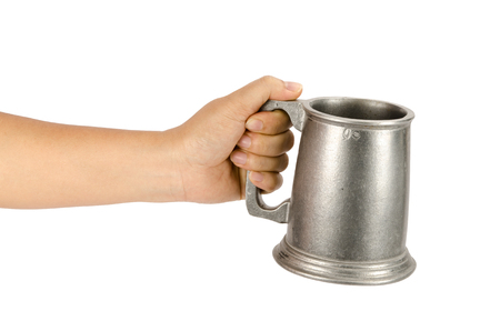 Image of old aluminum beer mug hold by hand on white background