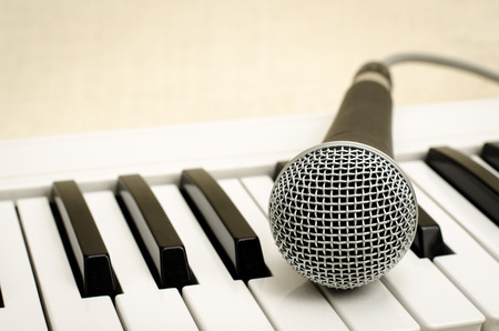 keyboard instrument: Image of keyboard with microphone on brown sack background Stock Photo