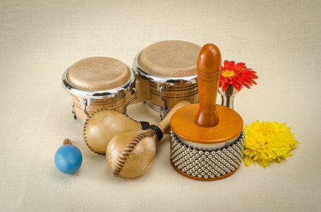 Image of latin percussion set with flower on brown sack background