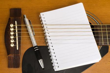 papier vierge: Image de papier blanc avec un stylo sur la vieille guitare acoustique