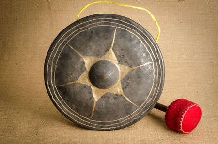 Thais ancient gong on brown sack background photo