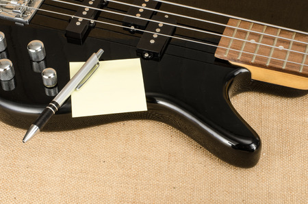 papier vierge: Blank paper with pen on electric bass guitar on brown sack background Banque d'images
