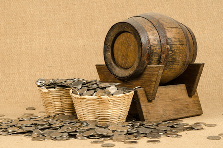 Stack of coins with wooden barrel on brown sack background photo