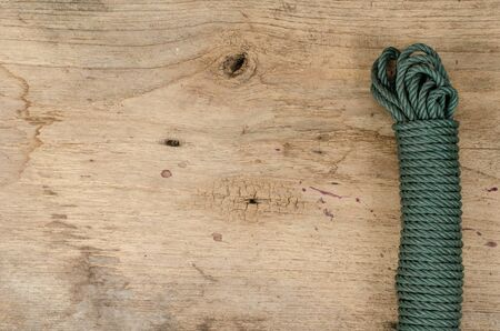 coiled rope: Coiled green nylon rope on old wood