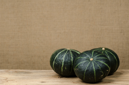 Mini green pumpkin on old wood with blurred brown sack background