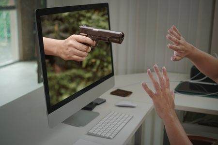 scare: Gun from sreen of computer with hands of scare man Stock Photo