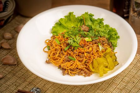 Chinese stir fried noodle with pork on white dish