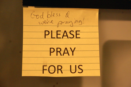 Pray request in all typed all caps with handwritten response.  PLEASE PRAY FOR US.  God bless & were praying.  Posted on a door in the Missouri State Capitol building.