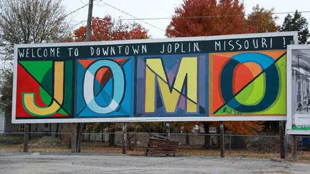 Colorful mural welcomes visitors to downtown Joplin, MO, in November 2017.  Fall foliage visible in the background.  Mural is located in a parking lot. Editorial