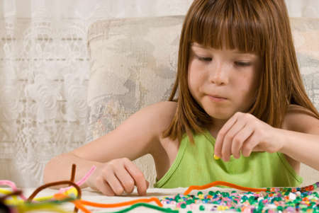 Young girl making bead bracelets photo