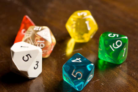 side lighting: Multicolored role play dice sitting on a wooden table top taken from a low angle. Side lighting and depth of field used to add drama to the photo.