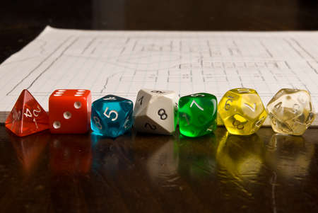 role play: A line of multicolored role play dice sitting in front of a game map drawn on graph paper. A shallow depth of field used to throw the background out of focus. Stock Photo