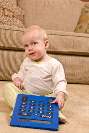 pj's: A young baby in a pair of generic PJs sitting on a living room floor with a large oversized calculator. The baby is looking up mischievously. Stock Photo