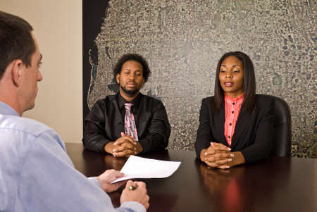 two persons only: A young African American couple about to sign papers or a contract.